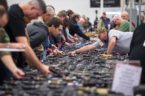 People examine handguns during The Nation's Gun Show in Chantilly, Virginia, on Oct. 3, 2015.