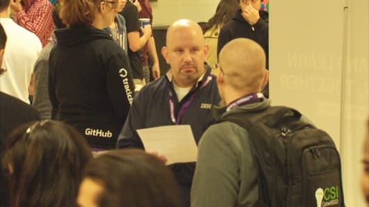 An IBM recruiter talks to students at a cybersecurity career fair at NYU Tandon School of Engineering.