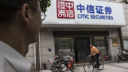 A man rides a bicycle past a Citic Securities Co. branch in Shanghai, China.