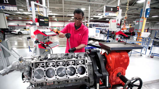 A woman works on an engine for a Dodge Viper at the Viper Assembly Plant in Detroit, Michigan.