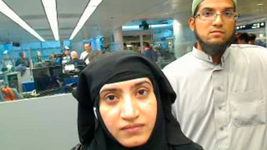 Tashfeen Malik, (L), and Syed Farook are pictured passing through Chicago's O'Hare International Airport in this July 27, 2014 handout photo.