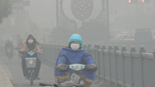 Cyclists wearing masks ride in heavy smog on Dec. 7, 2015, in Suzhou, China.