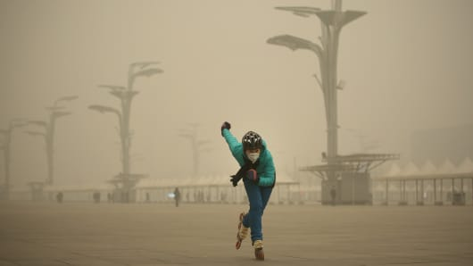 A woman wearing a mask practices Rollerblading at Olympic Park amid heavy smog on Dec. 1, 2015, in Beijing.