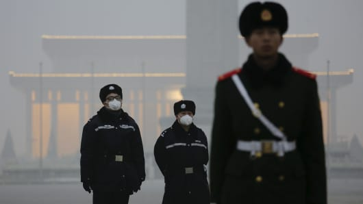 Policemen wear protective masks behind a paramilitary soldier at the Tiananmen Square on an extremely polluted day in Beijing, Dec. 1, 2015.