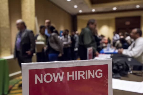 'Now Hiring' signage is displayed as job seekers wait in line to enter the San Jose Career Fair in San Jose, California.