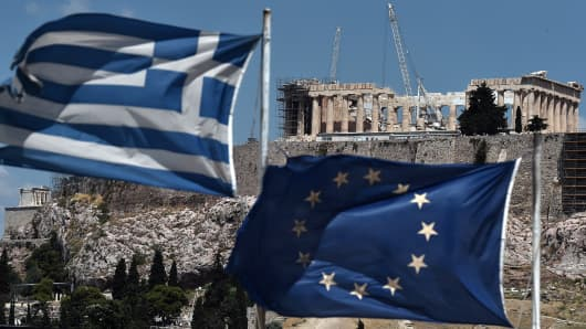 An EU and a Greek flag wave in front of the ancient temple of Parthenon atop the Acropolis hill in Athens.