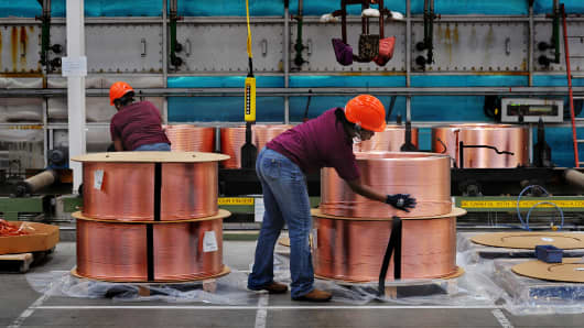 Factory workers secure large copper tube coils that will be wrapped and shipped out.