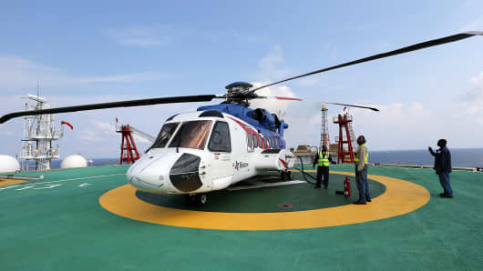 Employees wait for refueling to be completed on a passenger helicopter, operated by Bristow Group Inc., on the landing pad of the Agbami floating oil production.