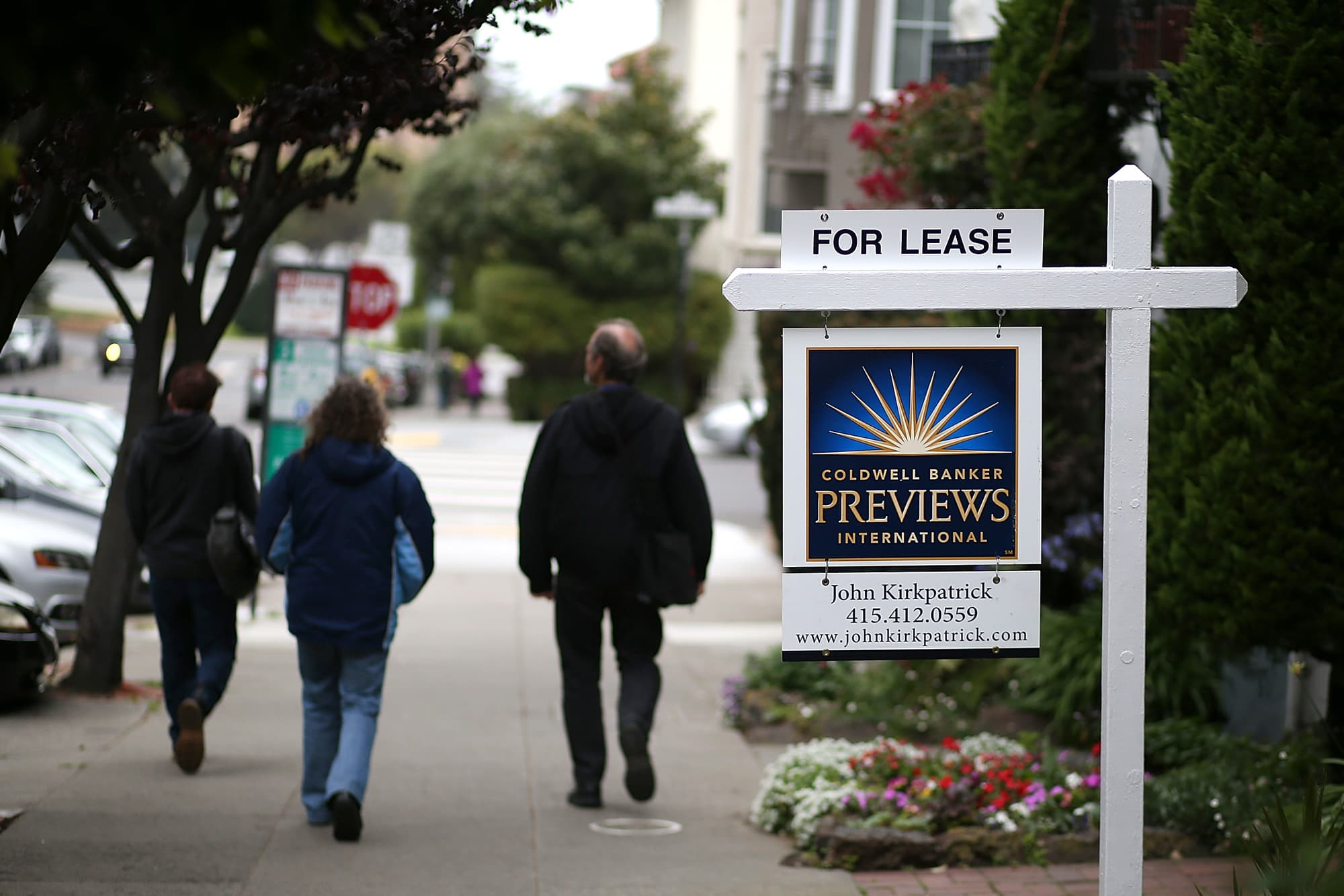 Pedestrians Walk By A For Lease Sign In San Francisco, California.