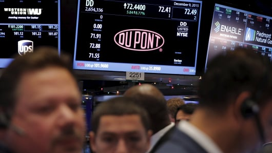 Traders work below a board displaying the DuPont logo on the floor of the New York Stock Exchange shortly after the opening bell in New York December 9, 2015.