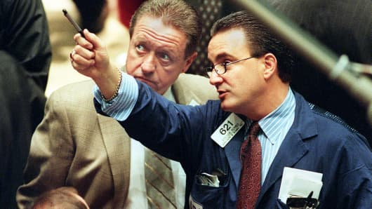 A day after the Dow Jones Industrial Average dropped over 231 points, traders on the floor of the New York Stock Exchange monitor early trading 13 October, 1999.