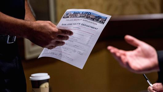 A job seeker reviews an employment application at the San Jose Career Fair in San Jose, California.