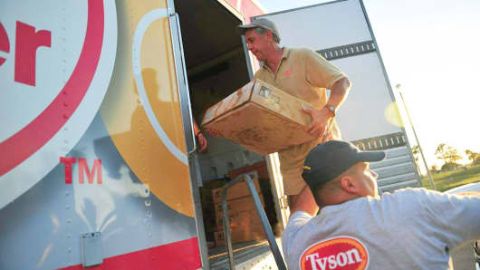 Tyson Food workers handle boxes of food for shipping.