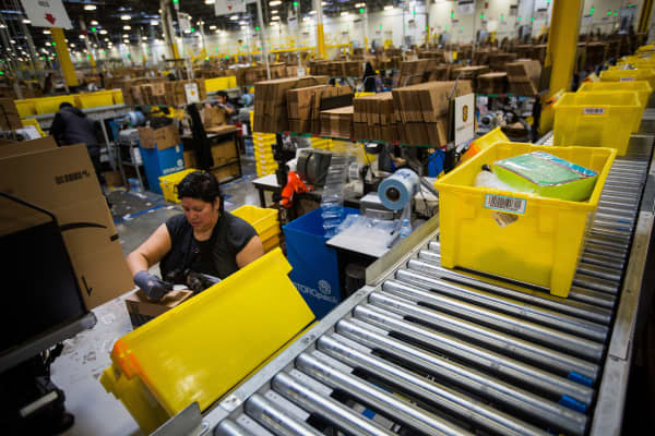An employee packs a box at the Amazon.com Inc. fulfillment center on Cyber Monday in Robbinsville, New Jersey.
