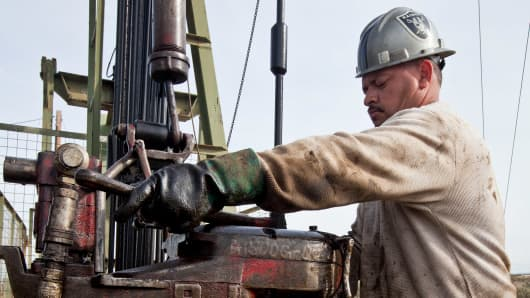 A floorhand operates a Chevron oil drilling rig near Taft, California.
