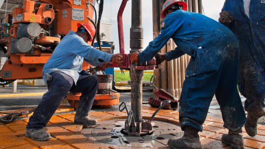 Oil workers make a pipe connection on a drilling rig near Encinal, Texas.