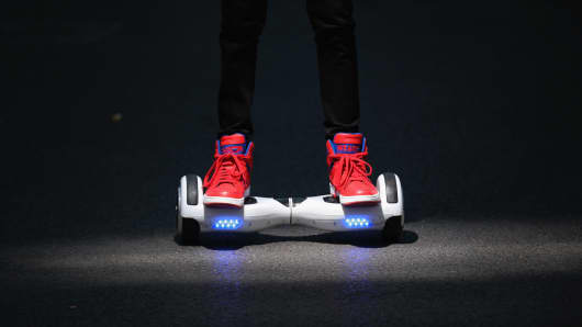 A youth poses as he rides a hoverboard, which is also known as a self-balancing scooter and balance board.