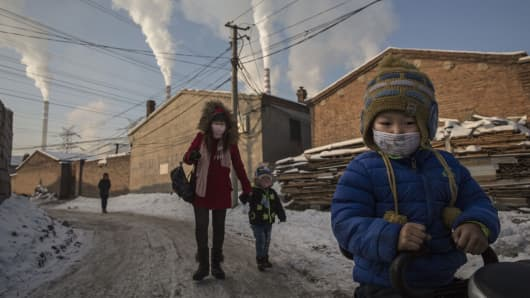 Chinese residents wear masks for protection as smoke billows from a coal fired power plant in Shanxi, China.
