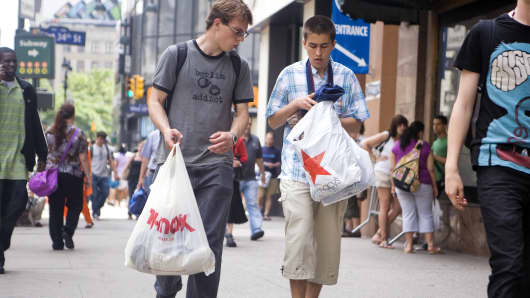 Shoppers walk with TJ Maxx and Macy's bags in Herald Square, New York.