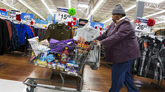 A woman pushes her shopping cart through a Walmart store in Secaucus, New Jersey.