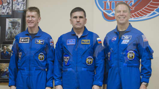 Expedition 46 Flight Engineer Tim Peake of the European Space Agency (ESA), Soyuz Commander Yuri Malenchenko of the Russian Federal Space Agency (Roscosmos) and Flight Engineer Tim Kopra of NASA pose for at the end of a press conference.