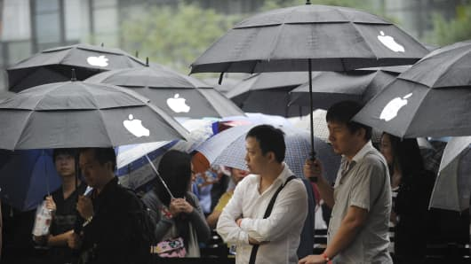 Apple customers queue up in the rain outside Apple's flagship store in Beijing.