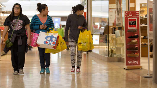 Shoppers carry bags while walking through the Cherry Creek Shopping Center in Denver.