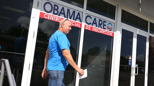 A man walks out of the UniVista Insurance company office after shopping for a health plan under the Affordable Care Act, also known as Obamacare in Miami.