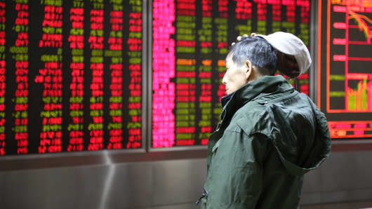 An investor observes stock market at a stock exchange hall in Beijing.