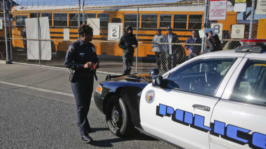 A Los Angeles School Police officer checks-in with officials at the LAUSD Gardena Garage where the fleet of school buses from around the district are parked while law enforcement investigates a threat against the district Dec. 15, 2015.