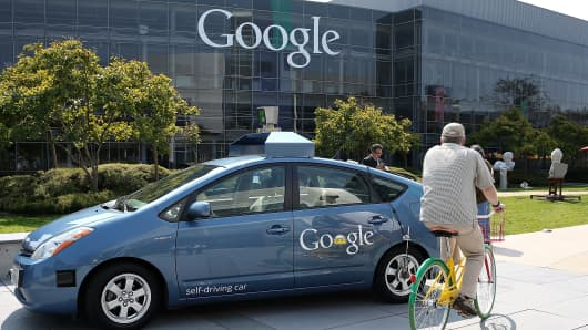 A bicyclist rides by a Google self-driving car at the Google headquarters.