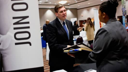 A company representative speaks with a job seeker during a Job Fair Giant career fair in Sterling Heights, Michigan.
