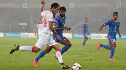 Delhi Dynamos FC Brazilian forward Gustavo Marmentini dos Santos (L) shoots the ball past FC Goa's Indian forward CS Sabeeth during the semi-final football match on December 11, 2015