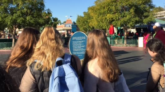 People at DisneyLand read a new sign in front which says no costumes, toy guns or selfie sticks.