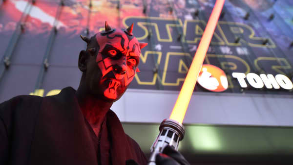 "A fan dressed as a Star Wars character poses in front of a movie theater to celebrate the opening of ""Star Wars: The Force Awakens"" in Tokyo on December 18, 2015."