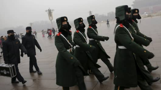 Paramilitary policemen wearing masks march on a cold morning amid heavy smog at Tiananmen Square in Beijing.