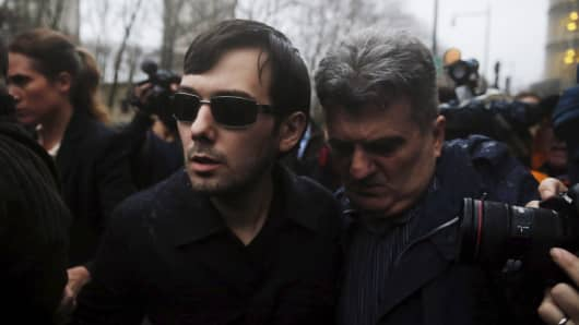 Martin Shkreli (C), chief executive officer of Turing Pharmaceuticals and KaloBios Pharmaceuticals Inc, departs U.S. Federal Court after an arraignment following his being charged in a federal indictment filed in Brooklyn relating to his management of hedge fund MSMB Capital Management and biopharmaceutical company Retrophin Inc. in New York