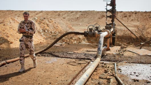 A member of the Syrian government forces walks next to a well at Jazel oil field, near the ancient city of Palmyra in the east of Homs province after they retook the area from Islamic State (IS) group fighters on March 9, 2015.