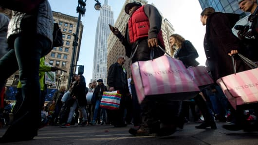 Pedestrians carry shopping bags on Black Friday through Herald Square in New York.