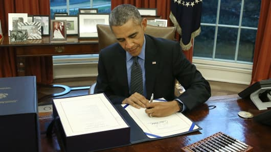 President Barack Obama signs the budget bill in the Oval Office of the White House December 18, 2015 in Washington, DC.