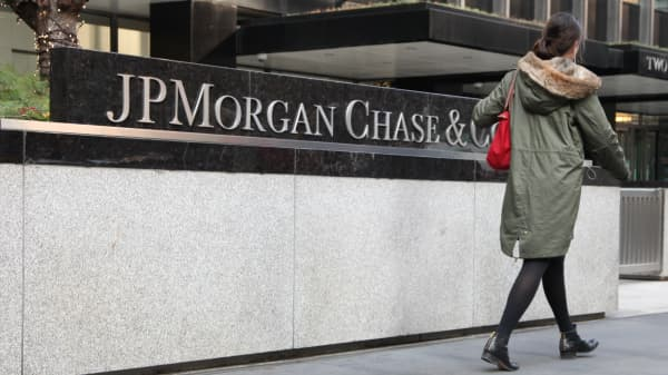 A pedestrian passes a sign in front of JPMorgan Chase headquarters in New York.