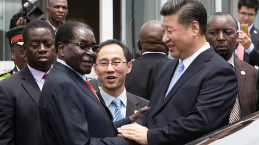 China's President Xi Jinping (2nd R) shakes hands with Zimbabwe's President Robert Mugabe (2nd L) as he arrives on December 1, 2015 in Harare.