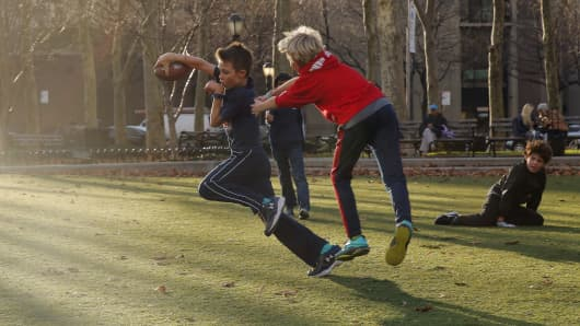 Young boys play in a park during an unusually warm winter day in the Brooklyn borough of New York December 15, 2015.