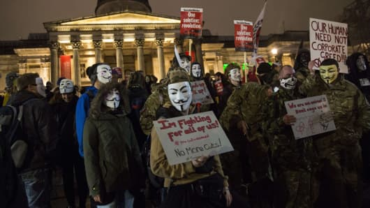 Anti-capitalist protesters wearing Guy Fawkes masks hold placards at the start of the 'Million Masks March', organised by the group Anonymous, in London.