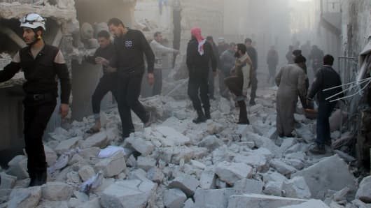 Syrians walk on debris of collapsed buildings after the war-crafts belonging to the Russian army carried out airstrikes on the opposition-controlled neighborhoods in Aleppo, Syria on December 11, 2015.