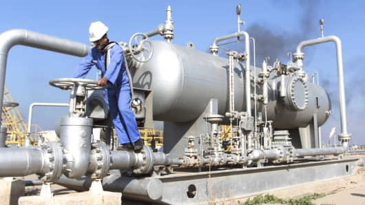 A worker checks the valve of an oil pipe at Nahr Bin Umar oil field, north of Basra, Iraq.