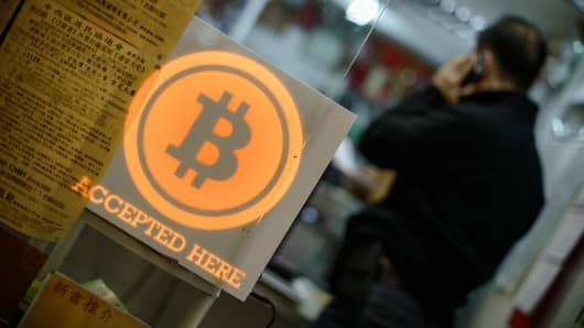 A man talks on a mobile phone in a shop displaying a bitcoin sign in Hong Kong.