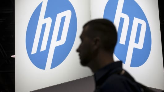 A man passes a Hewlett Packard display at a technology conference in Chicago.
