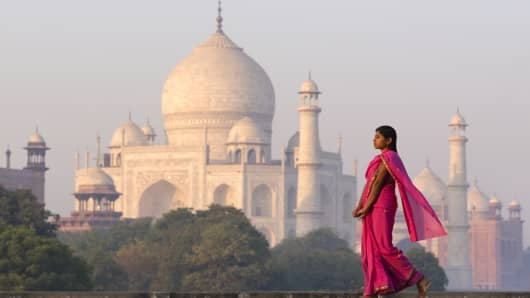 Young woman in pink sari with Taj Mahal in distance