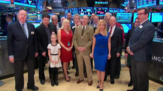 People singing on the floor of the New York Stock Exchange, Dec. 24, 2015.